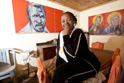 The Maboneng Township Arts Experience smiling lady in diningroom with art pieces on two walls