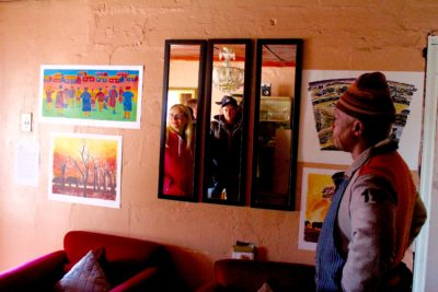 The Maboneng Township Arts Experience man show colourful art on wall