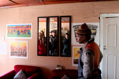 The Maboneng Township Arts Experience man show colourful art and mirrors on wall