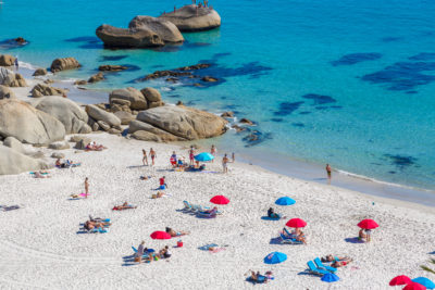 Clifton Beach red and blue umbrellas and people sunbathing