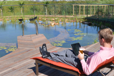Hotel Verde businessman relaxing on lounger outside next to pool